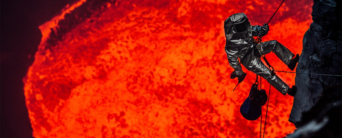 The Volcano Diver repelling into a lava lake wearing Newtex Proximity Suit Background Image